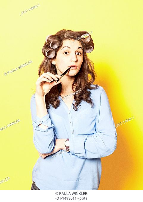 Portrait of confident young woman wearing hair curlers against yellow background
