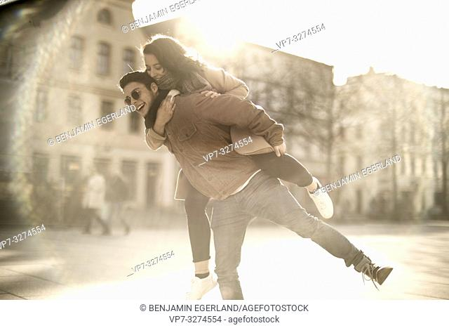 young upbeat teenage couple piggy back outdoors in sunlight in city, in Cottbus, Brandenburg, Germany