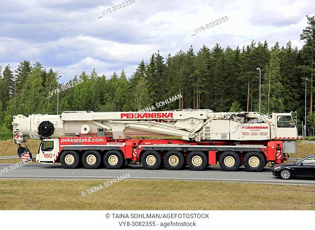 Side view of large Liebherr 8-axle mobile crane of Pekkaniska at speed on road with an overtaking car. Salo, Finland - June 8, 2018