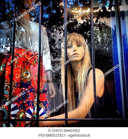 Sculptures of mannequins behind bars in a fashion shop in Prado del Rey, Sierra de Cadiz, Andalusia, Spain