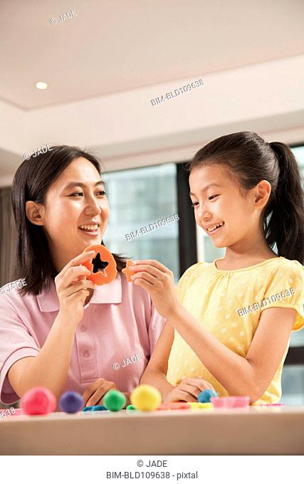Chinese mother and daughter playing with clay