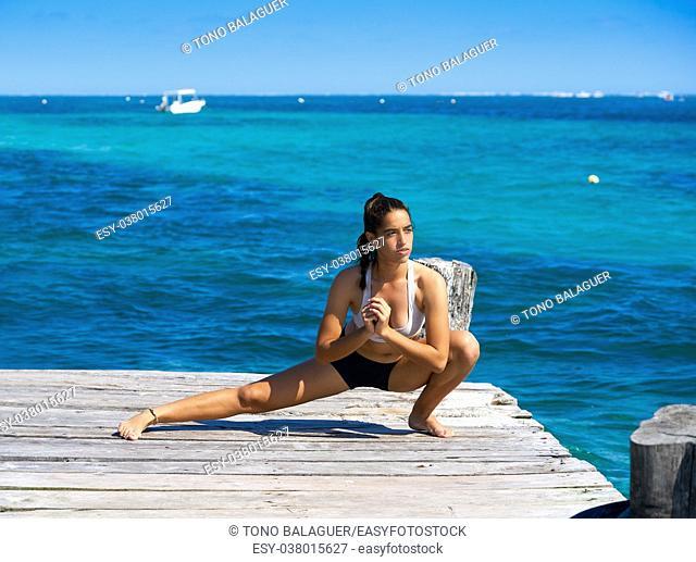 Latin athlete woman stretching in Caribbean beach pier