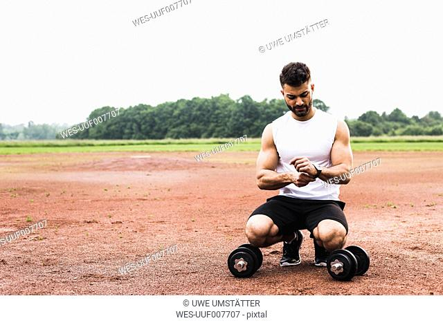 Athlete crouching with dumbbells on sports field