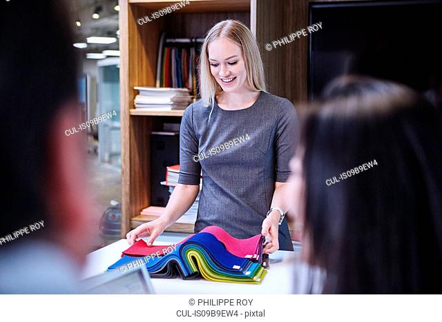 Woman looking at textile samples smiling