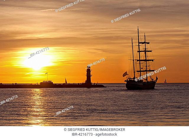 Sunset at harbor entrance, backlit sailboat, Hanse-Sail, Rostock, Mecklenburg-Western Pomerania, Germany