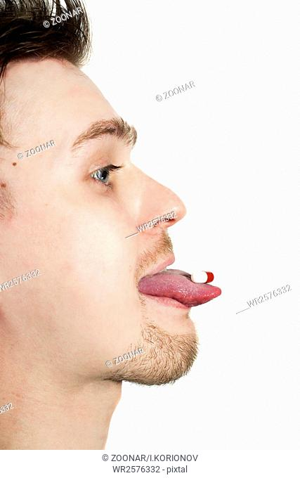 profile of young man with tablet on tongue