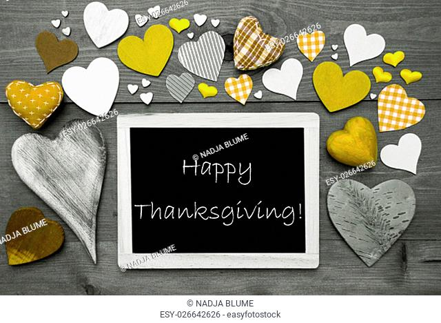 Chalkboard With English Text Happy Thanksgiving. Many Yellow Textile Hearts. Grey Wooden Background With Vintage, Rustic Or Retro Style