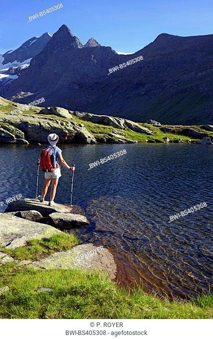 mountain wanderer standing at mountain lake Lac de Pareis near the Cirque Des Evettes, France, Savoie, Vanoise National Park
