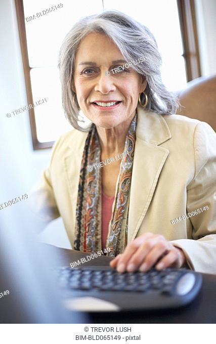 Confident businesswoman working on computer at desk