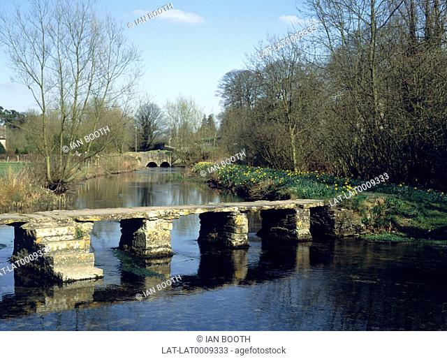 A stone Clapper bridge over the River Leach in April. Clapper bridges are one of the oldest forms of bridge,made from large slabs of granite resting on stone...