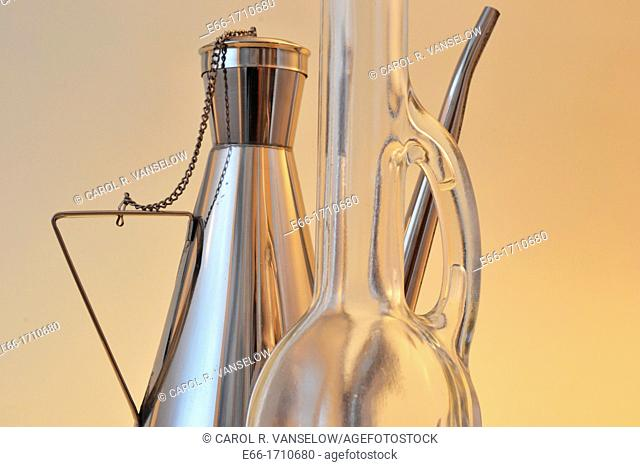 two olive oil bottles: one glass with long neck, one stainless steel