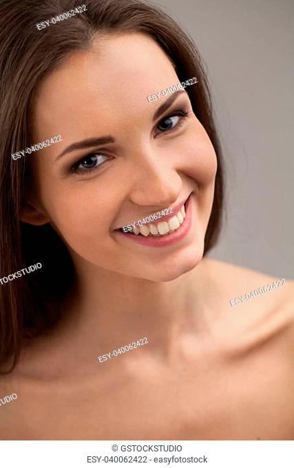 Fresh and beautiful. Top view of attractive young shirtless woman looking at camera and smiling while isolated on grey background