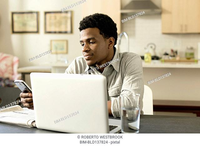Black businessman working at breakfast table
