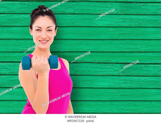 fitness woman with weight with green wood background