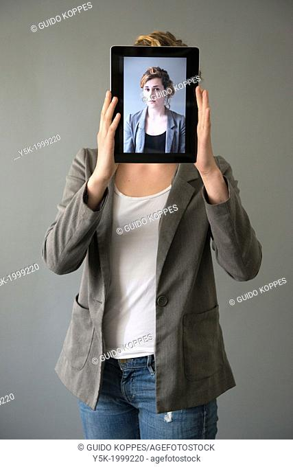 Tilburg, Netherlands. Young woman holding up an Digital Tablet, showing her portrait, which was taken earlier, in front of her face