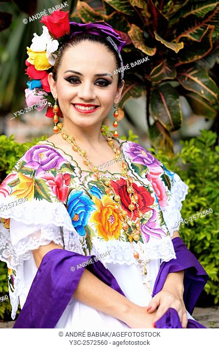 Young hispanic woman smiling while wearing Mexican folklore outfit