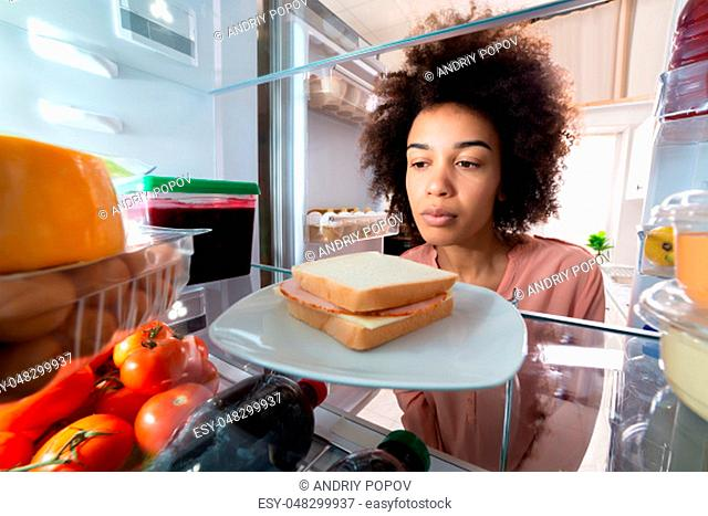 Close-up Of A African Young Woman Searching For Food In An Open Refrigerator