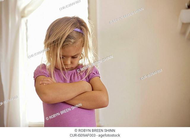 Young girl with head down and arms folded having tantrum