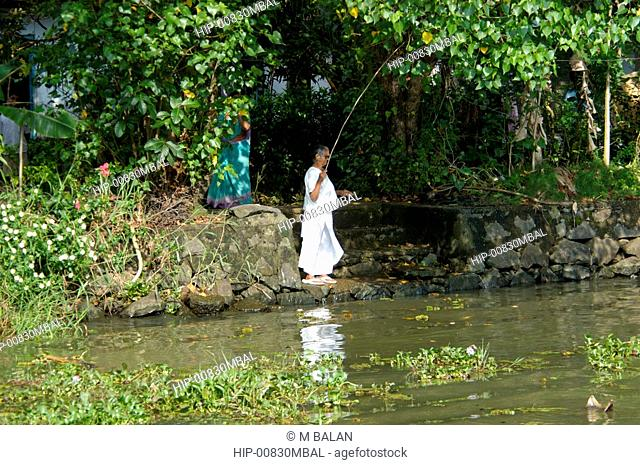 LOCAL LADY FISHING IN BACKWATERS OF NEDUMUDI, KUTTANAD, KERALA