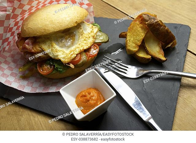 Beef burger with fried egg and chips