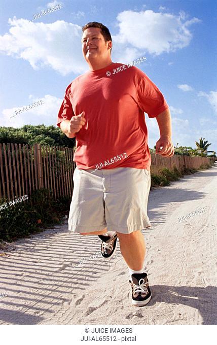 Overweight man running on beach