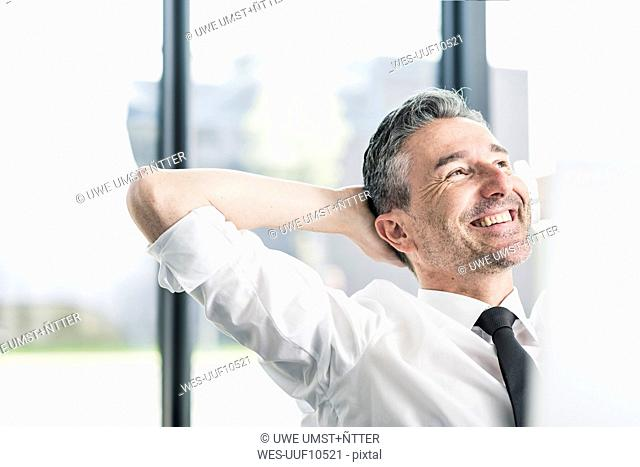 Portrait of content businessman relaxing in his office