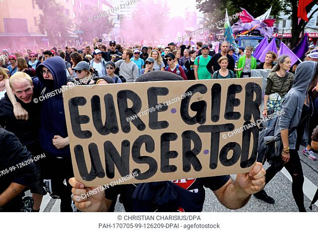 Participants of a demonstration against the upcoming G20 Summit walk across the Reeperbahn and hold up a sign saying 'Eure Gier ist unser Tod' (lit