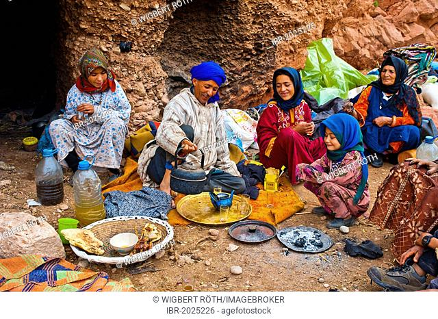 Nomadic cave-dwellers sitting in front of their cave-dwelling, a man wearing a blue turban is pouring tea into a pot on a copper tray