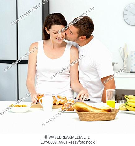 Passionate man kissing his girlfriend while cutting bread for breakfast in the kitchen