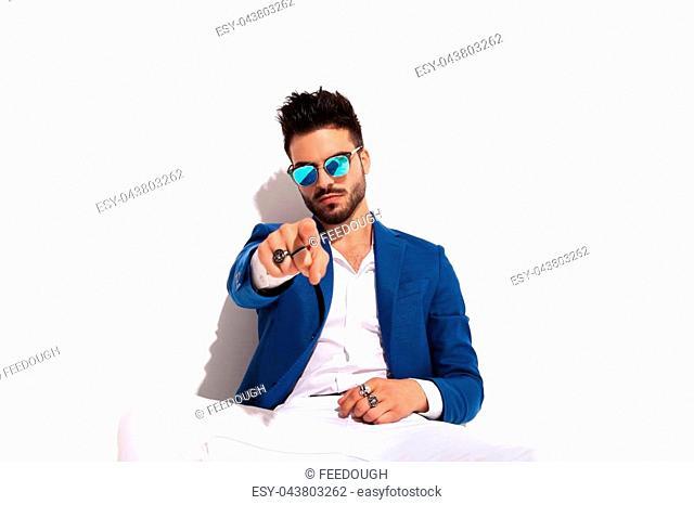 seated fashion elegant man pointing finger to the camera on white background