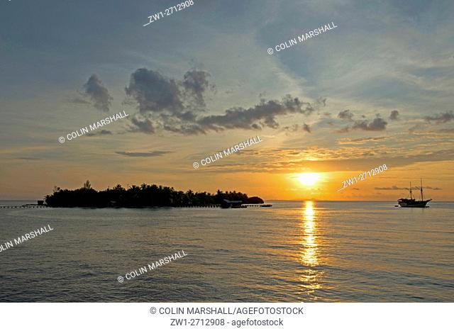 Boat at sunset, with silhouettes of islands, Raja Ampat (4 Kings) area, West Papua, Indonesia
