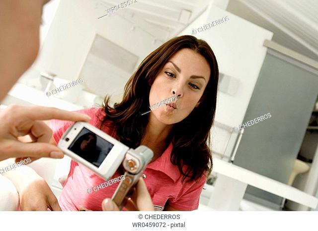 Person taking a picture of a mid adult woman with a mobile phone