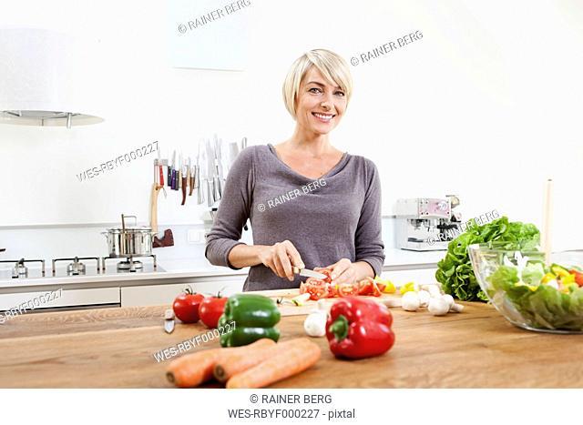 Germany, Bavaria, Munich, Woman preparing food in kitchen