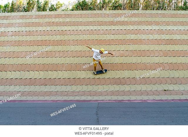 Young man riding skateboard on a wall