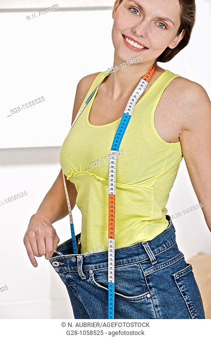 young smiling woman holding her too large jeans after slimming,dieting, with a measuring tape around her neck,looking at camera