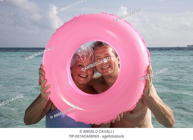 Maldives, Ari Atoll, senior couple holding a pink inflatable ring
