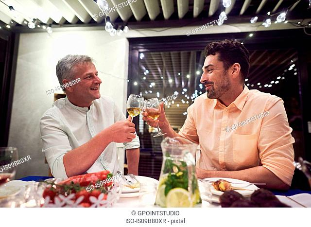 Two men sitting at dinner table, holding wine glasses, making toast