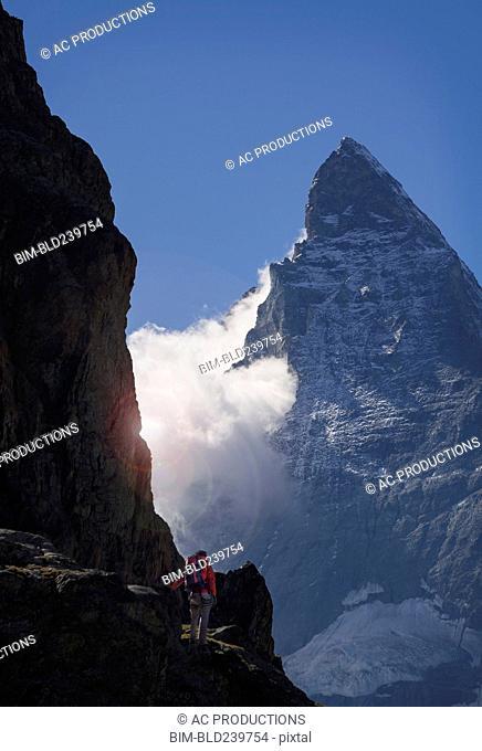 Man hiking in mountain near clouds