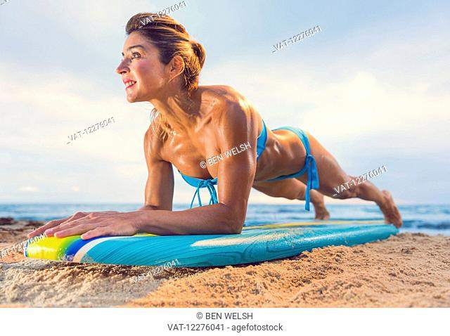 Woman exercising on a surfboard; Tarifa, Cadiz, Andalusia, Spain