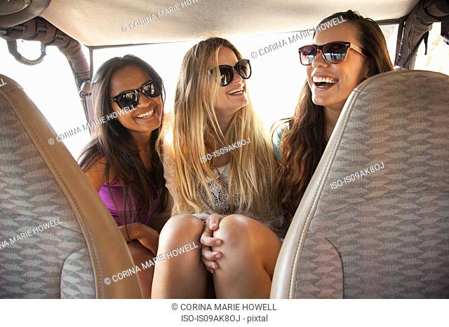 Three young women laughing in back seat of car