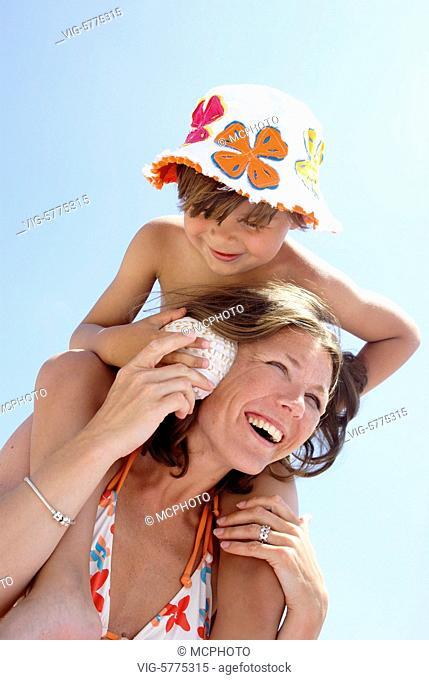 Ein kleiner Junge haelt seiner Mutter eine Muschel ans Ohr, Mittelmeer, Spanien| A little boy put a shell on the ear from his mother - Menorca, Balearen, Spain