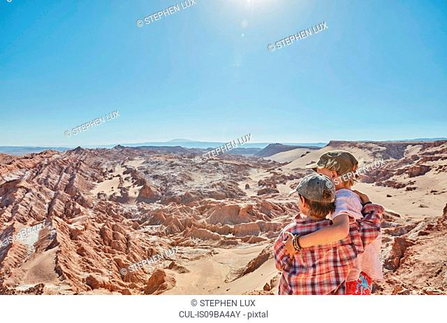 Boy and his brother looking out over desert landscape, Atacama, Chile