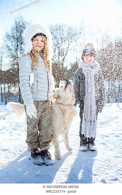 Brother and sister posing with dog