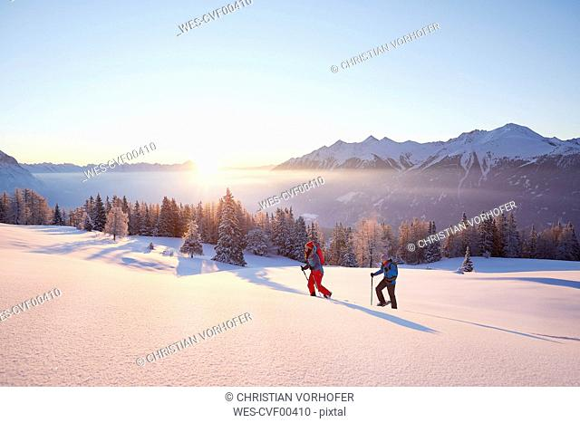 Austria, Tyrol, snowshoe hikers at sunrise
