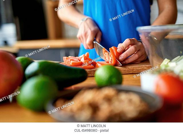 Hands of young woman at kitchen table slicing tomatoes