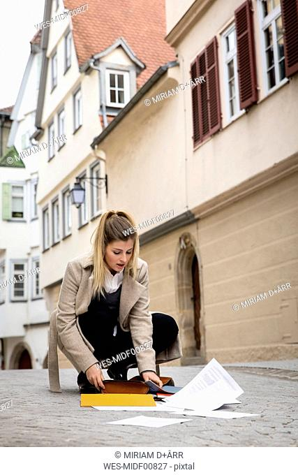 Germany, Tuebingen, young woman collecting documents on the street