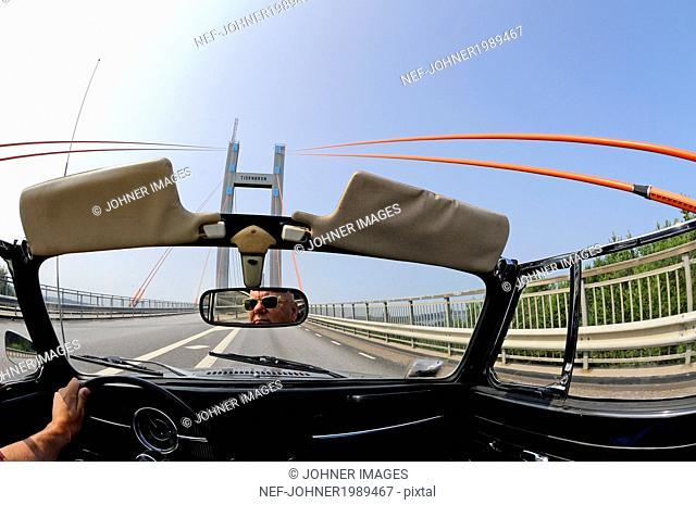 Person in convertible car driving through bridge