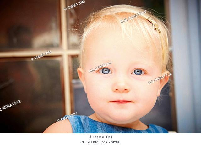 Portrait of cute blonde baby girl looking at camera