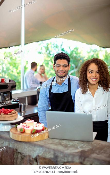 Male waiter and female waitress with laptop