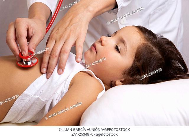 Pediatrician in white lab coat examines little girl